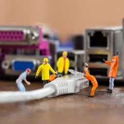 Conceptual image of miniature engineer and worker plug-in lan cable to computer