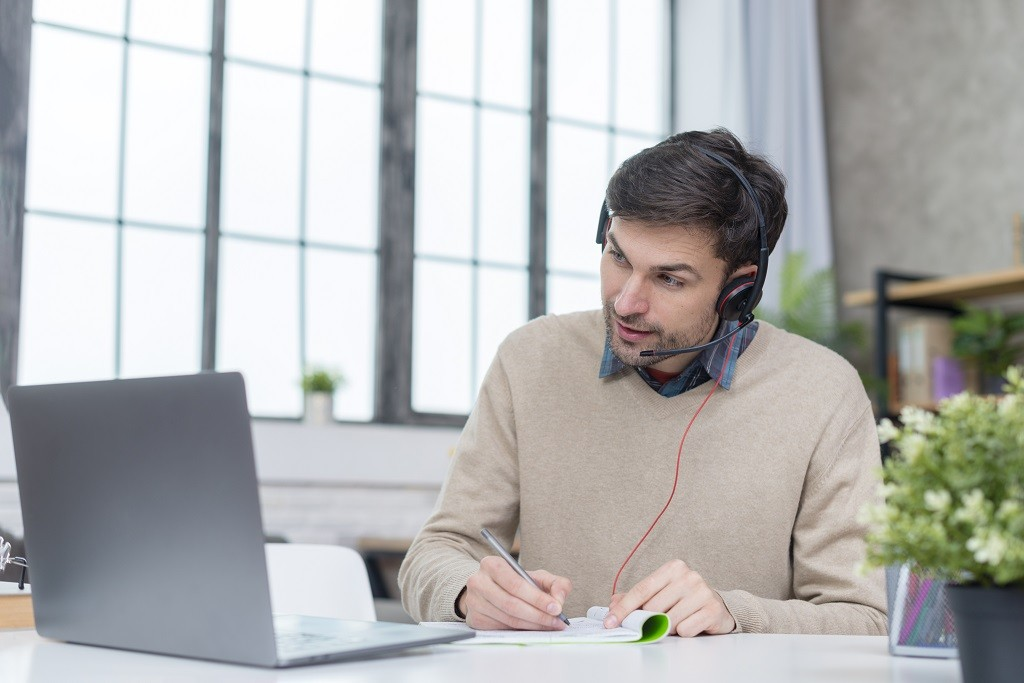 man with headphones having online meeting